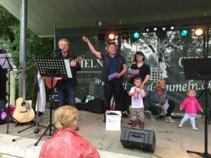"""Pastor Uwe Winkler (2. v.li.), Stiftungsvorstand und Vorsitzender der Ummelner Gemeinschaft, ruft zum Abschluss des Kids Days zum """"Rudelsingen"""" auf."""