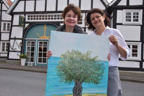 Die Künstlerin udn eine Mitarbeiterin der Anker Villa zeigne ein Bild.